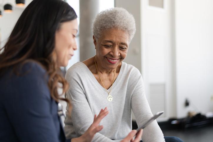Een jonge mantelzorger die een oudere vrouw binnenshuis helpt met haar tablet. Ze glimlachen allebei.