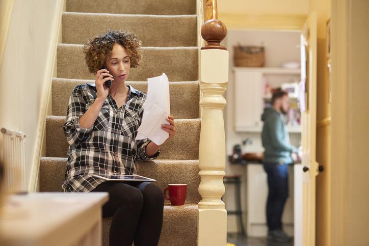 een vrouw zit op de trap van haar huis en belt de klantenservice om een rekening te controleren die ze heeft ontvangen. Op de achtergrond komt haar partner kijken wat er aan de hand is.
